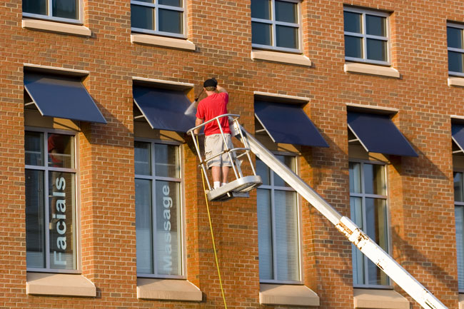 Worker on a crane pressure washing a building facade