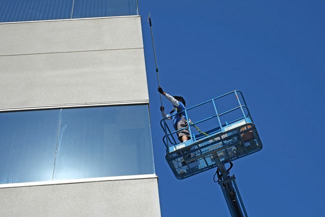 Worker on a crane trying to reach difficult windows to clean