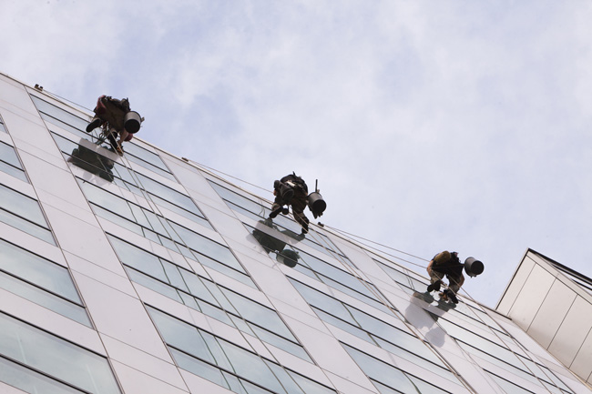 Three workers with harnesses and buckets washing the windows of a building