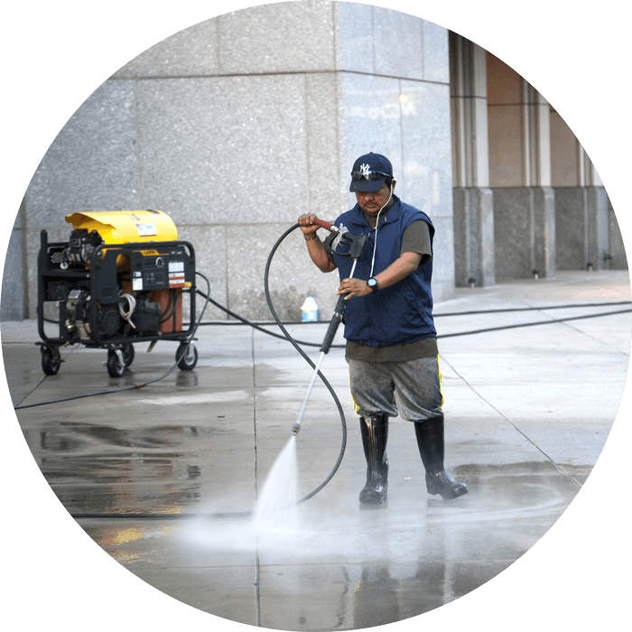 Worker with a pressure washing machine cleaning a floor