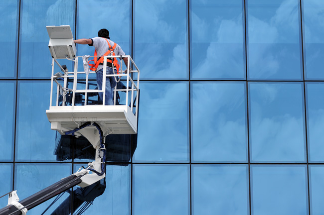 Worker on a crane cleaning windows of a building