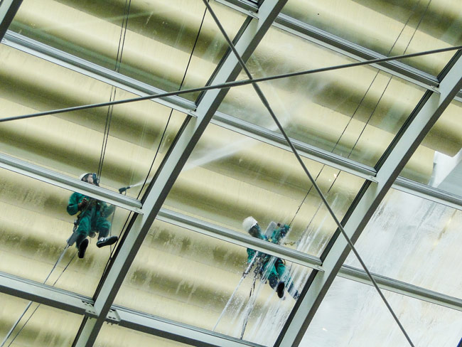Two workers with pressure and steam machines cleaning a glass roof top