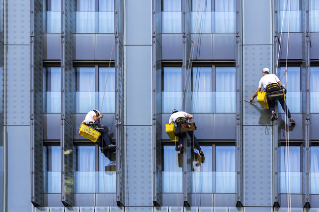 Three workers with harnesses and cleaning equipment cleaning a building's facade
