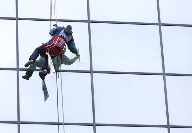Worker washing building windows with harness
